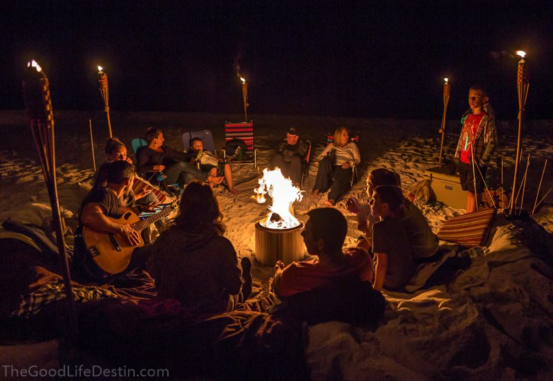 Family and friends gathered around a beach bonfire using a solo stove fire pit in Miramar Beach Florida
